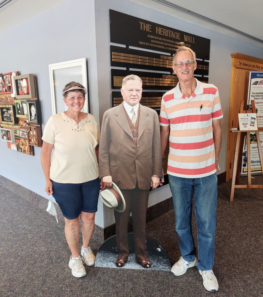 Betty and Dan standing with a cardboard cutout of Herbert Hoover.