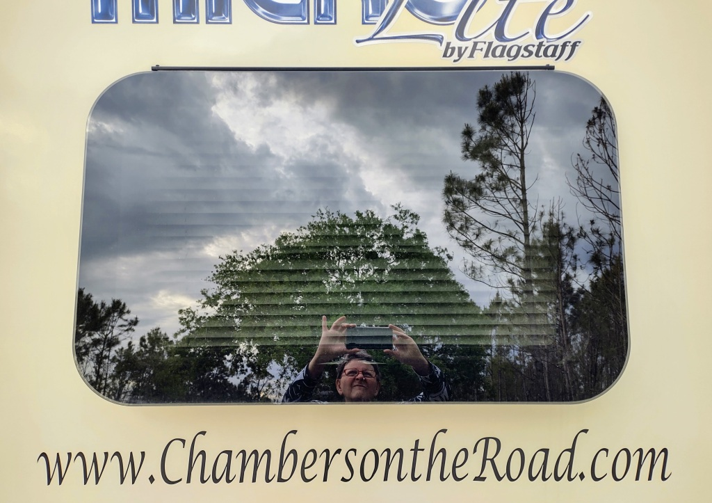 View of back window of travel trailer with reflection of trees and clouds, along with me taking the photo.