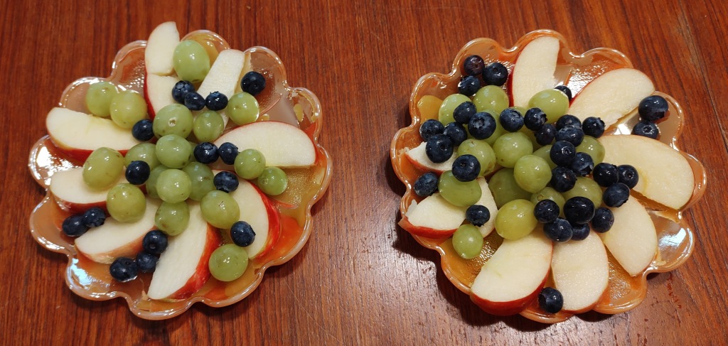 Two bowls of fresh fruit - grapes, apples and blueberries.
