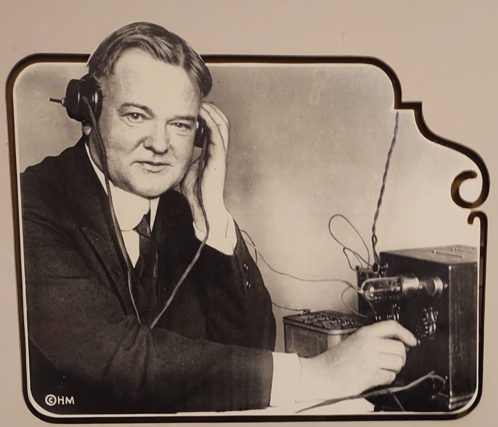 Herbert Hoover with a small radio receiver.
