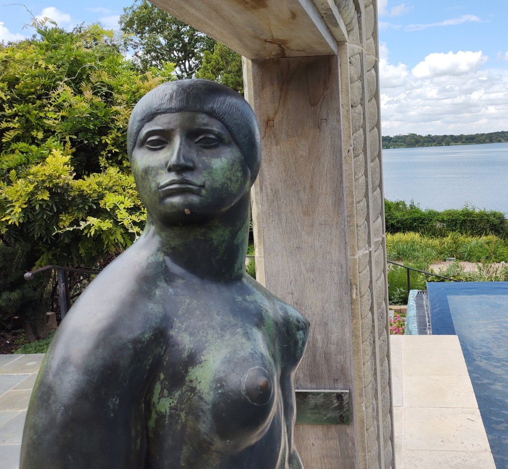 Nude bronze statue of a woman with a lake in the background.
