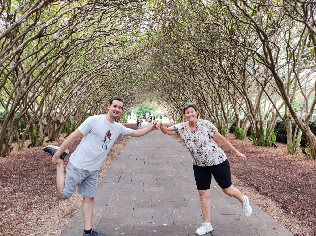 Michael and Betty in a fun pose with a canopy of trees in the background.