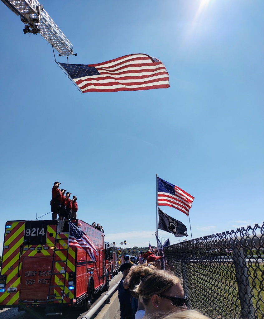 Firefighters salute as funeral procession passes by.