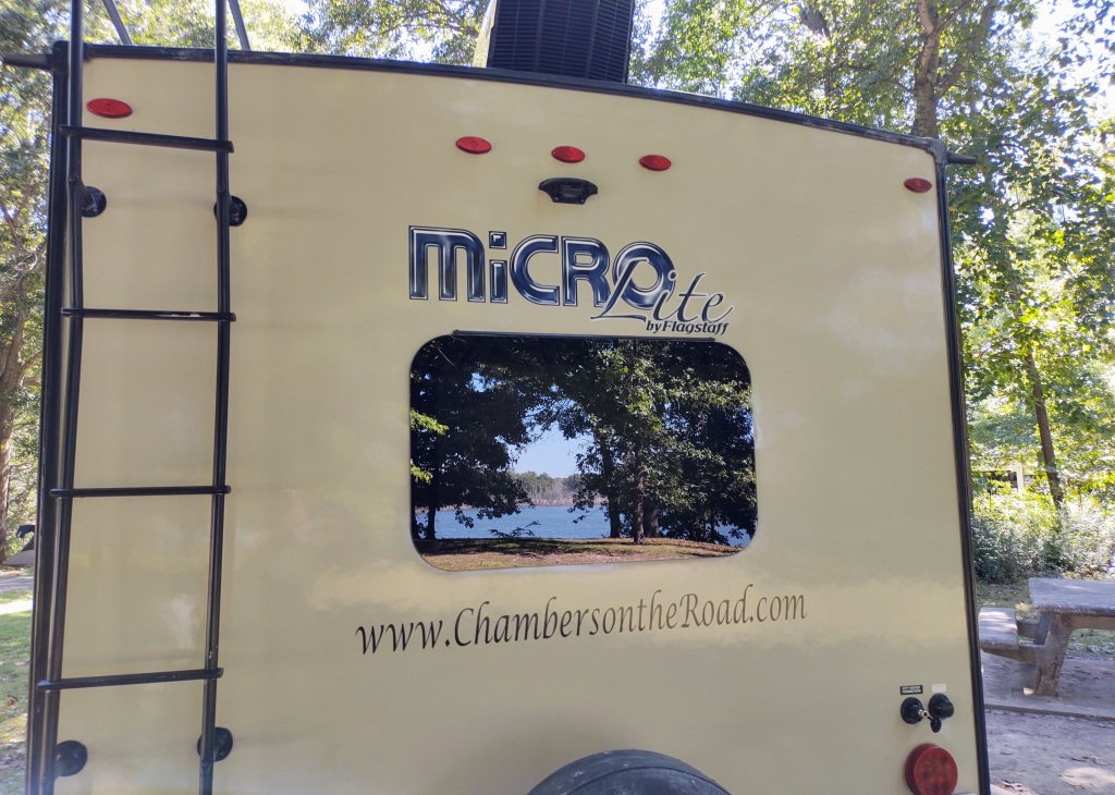 Back of Micro Lite with lake and trees reflected on the back window.